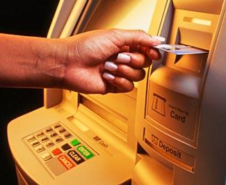 Egy bankautomata látható a képen, amint egy ember éppen belehelyezi a kártyáját