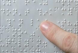 A képen egy Braille-lap látható, amint valaki a kezével olvassa