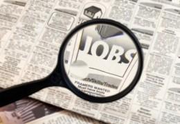 A képen egy nagyító látható, amivel egy ember keres valamit és egy munkák feliratot talál