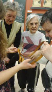 A látógatócsoport néhány tagja egy kiállítási tárgyat tapint