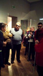 A klubtagok a múzeum egyik kiállítótermében hallgatják a tárlatvezetést