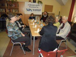 A képen a kispesti klub tagjai láthatóak egy asztal körül és Mohay Orsolyát hallgatják