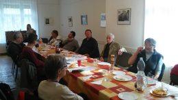 A fényképen a klubdélután egy pillanata látható, terített asztal és a tagok
