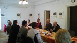 A fényképen a klubprogram egy pillanata látható, amint a tagok az asztal mellett ülve hallgatják azt, aki beszél