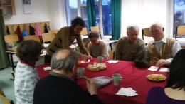 A tagok asztal körül ülve mesélik az ünnepi élményeiket