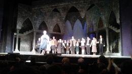 A képen a színházi előadás látható, színészekkel teli a színpad