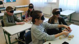 A rákosmenti érzékenyítésen a padsorokban ülő diákok feladatokat oldanak meg, szemtakaróval
