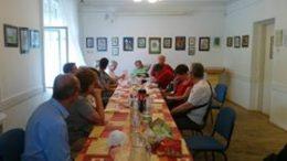 a képen a tagok az asztal körül