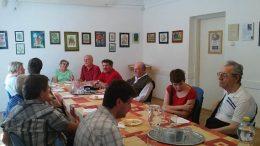 A képen a tagok ülnek az asztal körül