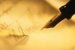 A képen egy elegáns toll látható, amint egy papírra írnak vele
