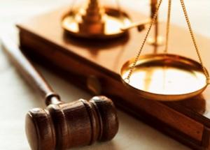 A képen kalapács és mérleg látható, mint ami a bírói igazságszolgáltatás jelképe