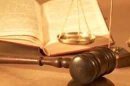 A képen kalapács, törvénykönyv és mérleg látható, mint ami a jogszolgáltatás jelképei