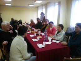 A klubtagok hallgatják az élménybeszámolókat egy asztal körül ülve