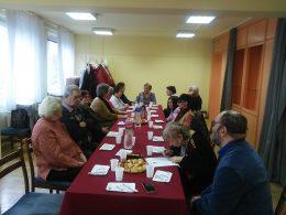 A képen a klubtagok egy asztal körül ülve beszélgetnek