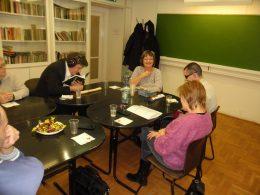 A klubtagok egy nasival teli asztal mellett beszélgetnek