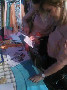 Érdeklődő lányok vizsgálgatják egyik kezükkel a Braille-feliratot az előttük lévő szoknyán, közben másik kezükben a sík-Braille ABC segítség gyanánt.