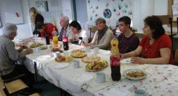 A képen a februári klubnap egy pillanata látható, amint az asztal körül ülnek a klubon jelenlévő emberek