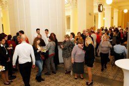 A képen az látható, amint a konferencia résztvevői a folyosón berendezett kiállításokat nézik meg