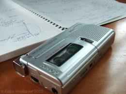 A képen egy diktafon és egy jegyzetfüzet látható