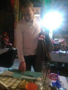 A képen az látható, amint egy látogató nézi a braille-írással ellátott ruhákat