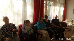 A képen az látható, amint az ablak mellett ülve hallgatják a programot a résztvevők