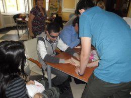 A fényképen a kiállítás látogatásának egy pillanata látható, amint a látogatók origamit hajtogatnak