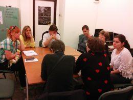 A fényképen a beszélgetés egy pillanata látható, amint egy asztal köré ülve mindenki elmond egy saját történetet
