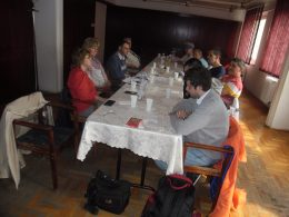 A képen az látható, amint a résztvevők egy asztal körül ülnek le