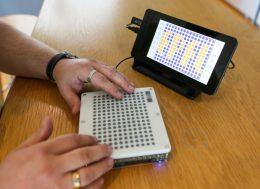 A képen az eszköz fényképe látható, amint valaki használja és az ujjával tapintja a rögtönzött térképet