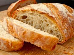 A képen egy finom sütött kenyér képe látható, amint szeleteltek belőle egy darabot