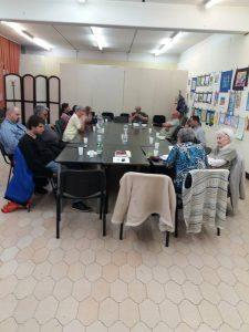 A fényképen az látható, amint a megjelentek leülnek az összetolt asztalok köré