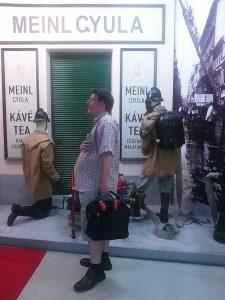 A képen egy tagunk látható, a hátterében régi tűzoltók által használt ruhák, melyek bábukon vannak
