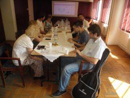 A képen az látható amint a tagok az asztal körül ülnek és hallgajták Jani zenéjét