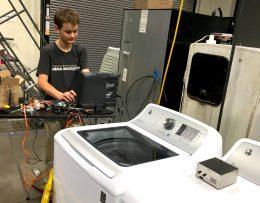 A képen a 14 éves fejlesztő látható, amint egy számítógépen a mosógépek digitális vezérlőihez programot készít