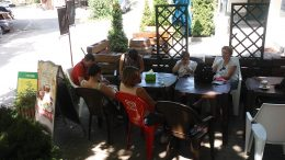 A képen az látható, amint a kirándulók egy része a cukrászdában ül és fagyiznak
