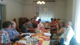 A képen a klub résztvevői látszanak, amint egy asztal előtt ülnek