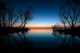 A hangulatfotó, amit ehhez a néhány sorhoz választottam kifejezetten lírai. Egy tiszta-vizű, csendes tó tükörsima felületét látjuk, amin a jobb és bal oldalt benyúló kis tőzeges sziget kopár, fekete fáinak bozontos ág-boga köszön vissza homályosan. Pirkad, az ég alja a távolban már rózsaszínes árnyalatba fordul, a látóhatáron lágyan megkettőződve a tavon. Az ágak sűrűje kontrasztos karcolatként festi meg a színes hátteret. A horizont vonala fölött és alatt még sötéten kéklik az éjszakai égbolt és jegesen sima víz, amelyen elhagyottan lebeg egy aprócska fadarab.