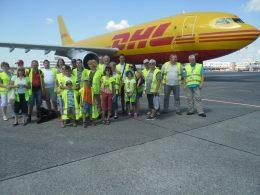 A képen a csoport látható egy DHL szállítógép előtt