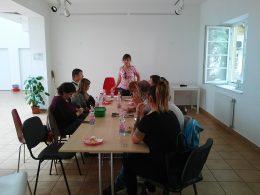 A képen a hallásvizsgálatról és a hallásról beszélgetünk egy asztal körül ülve