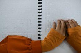 A képen egy kisgyermek keze látható, aki braille-írást olvas a kezecskéjével