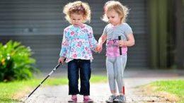 A képen 2 vak kislány sétál