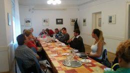 A képen a klubnap egy pillanata látható, ahol a klubtagok egy asztal körül ülnek