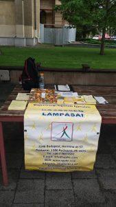 A képen a piaci asztalunk látható, a lámpás klubot hirdető plakáttal