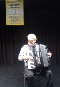 A képen Weszely Ernő látható, amint a könyvátadó ünnepségen harmónikázik