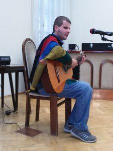 A képen Domoszlai János látható gitározás és éneklés közben