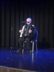 A képen Weszely Ernő látható, fellépése közben, ülve harmónikán játszik