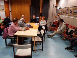 A képen a tagok egy asztal körül ülnek