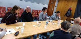 A tagok egy hosszú asztal körül ülve hallgatják az előadást