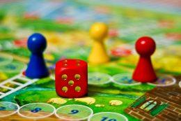 A képen egy dobókocka és bábuk láthatóak, melyek a társasjátékok kellékei