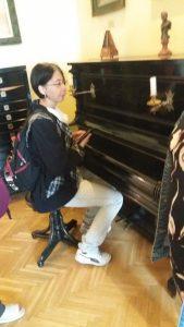 A képen: Erika ül egy zongora elött